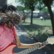 Teenager tossing hair while playing guitar — Stock Photo