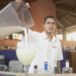 Hispanic male bartender pouring a pina colada — Stock Photo