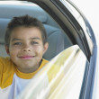 Portrait of boy looking out car window - Stock Photo