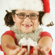 Young girl in a Santa hat holding out a tiny present — Stok fotoğraf