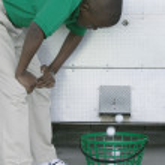 jeune garçon flexion vers l'avant en regardant une distributrice de balle de golf sur un terrain de golf — Photo
