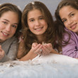 Stock Photo: Hispanic sisters laying on bed with down feathers