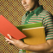 Young man holding multicolored books — Stockfoto