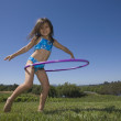 Portrait of girl in bikini playing with hoola hoop — Stock Photo