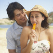 Royalty-Free Stock Photo: Young man hugging his girlfriend as she eats a popsicle