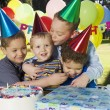 Stock Photo: Group of boys hugging at birthday party