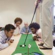 Businesspeople playing golf in office — Stock Photo