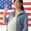 Pregnant Chinese woman in front of American flag — Stock Photo #13226093