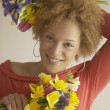 Stock Photo: Young African woman holding bouquets of flowers and smiling