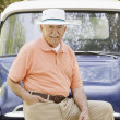 Portrait of elderly man leaning on old pickup truck — Stock Photo