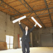 Businesswoman cheering in empty warehouse with blueprints — Stock Photo