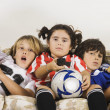 Group of children in sports gear watching television on the sofa — Stock Photo