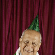 Smiling man in party hat - Stock Photo