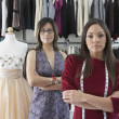 Dressmakers standing beside mannequin in clothing store — Stock Photo