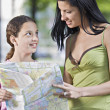 Mother and daughter consulting a map - Stock Photo