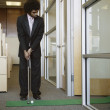 Businessman playing golf in office — 图库照片