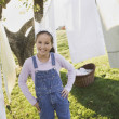 Pacific Islander girl smiling next to laundry on clothesline — Stock Photo