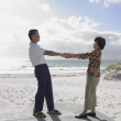 Asian holding hands on the beach — Stock Photo