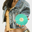 Studio shot of a young woman holding a CD — Stockfoto