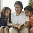 Mother reading to daughters - Stock Photo