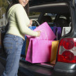 Stock Photo: Pacific Islander woman putting shopping bags into car