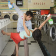 Couple dancing with soap in laundromat - Foto Stock