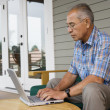 Profile of elderly man sitting at table typing on laptop — Stock Photo #13226410