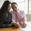 Couple holding hands while signing a document — Stock Photo