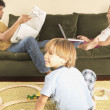 Parents on sofa and young son playing with trains on floor - Stock Photo
