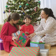 Family opening gifts on Christmas day in front of tree — Stock Photo