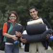Indian couple carrying camping supplies — Stock Photo
