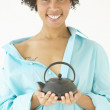 Portrait of woman holding tea kettle — Stock Photo
