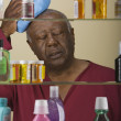 Sick senior African man in front of medicine cabinet - Stock Photo