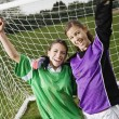 Two friends cheering in front of soccer net — Stock Photo #13226558