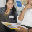 Young woman conversing with man in meeting — Foto Stock