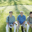 Golfers sitting on bench — Lizenzfreies Foto