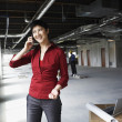 Woman on mobile phone at construction site — Foto Stock