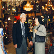 Senior couple holding hands in lighting store — 图库照片