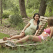 Two young women sitting on lounge chairs - Stock Photo