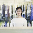 Asian drycleaner standing behind counter  — Stock Photo