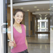 Portrait of businesswoman opening door — Stockfoto