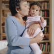 Middle-aged woman kissing her baby granddaughter — Stock Photo #13226709