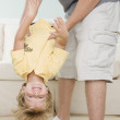 Father holding young son upside down - Stok fotoğraf