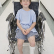 Boy with broken let sitting in wheelchair in hospital corridor — Stock Photo