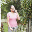 Young woman talking on her cell phone outdoors - Stock Photo