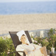 Woman in lounge chair at beach hotel — Stock Photo #13226779