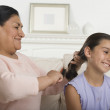 Royalty-Free Stock Photo: Hispanic grandmother brushing granddaughter\'s hair