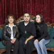 Stock Photo: Three Hispanic family members sitting on antique sofa