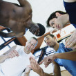 Low angle view of coach with basketball players in huddle — Stock Photo