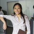 Stock Photo: Asibusinesswomleaning on cubicle wall